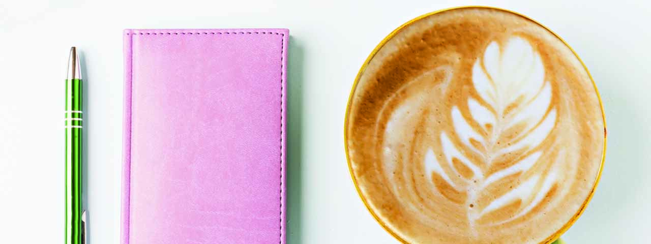 Green pen, pink agenda, latte art with leaf-shaped milk foam